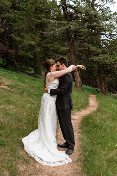 Bride has her arms our stretched on the grooms shoulders and they are standing on a trail