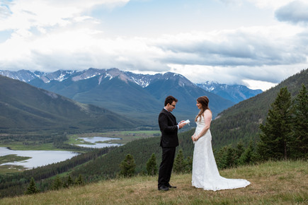 Bride and groom exchanging vows that are hand written in a booklet over looking Banff National Park.