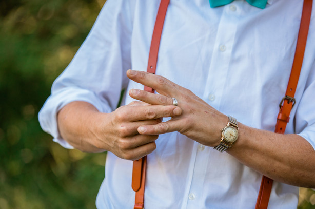 grooms hands and he is holding his wedding band that is around his finger.