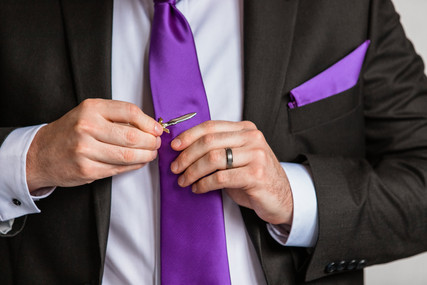 Groom placing a tie clip on his tie, also show casing his wedding band. Tie and boutonniere are purple.