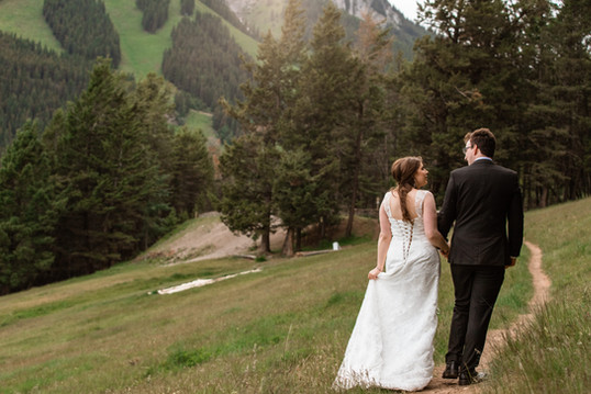 Bride and groom walking on a trail down a hill of beautiful trees