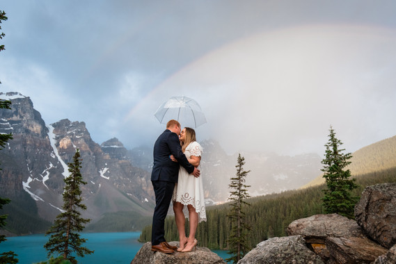Bride and groom standing under an umbrella with a rainbow behind them.