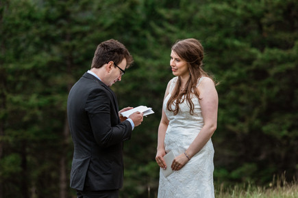 Bride and groom exchanging personalized vows that are hand written in a booklet at Banff National Park.