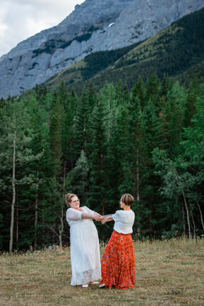 Bride and maid of honour playing, holding hands and spinning. Big beautiful trees behind them.