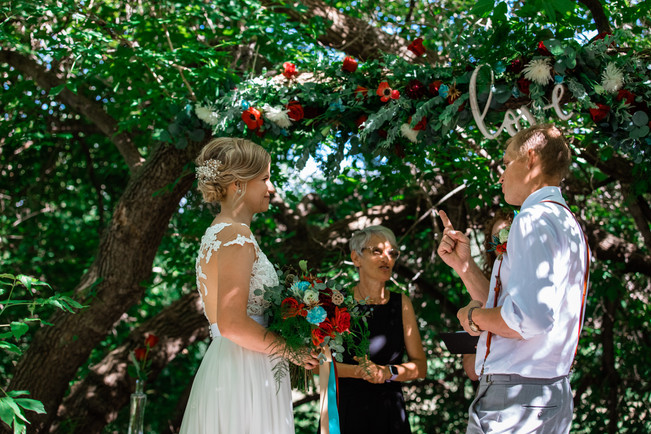 bride and groom under a bid tree signing vows to one another.