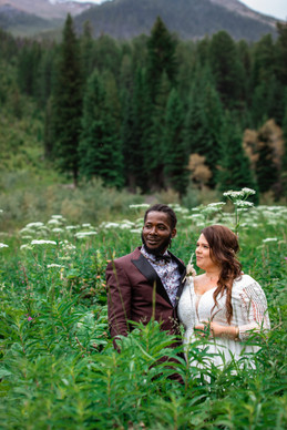 Bride and groom standing in a field of wild flowers.