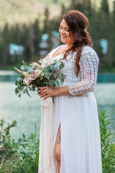 Bride standing in front of the lake holding her bouquet.