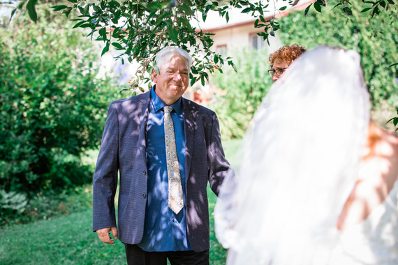 Bride turning around to see her parents in her dress for the first time during the first look.