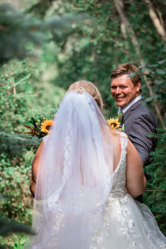 Photo of the groom looking at his bride with a big smile on his face.