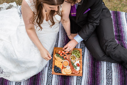 Bride and groom sitting on a blanket having a charcuterie board picnic at Cascade ponds.
