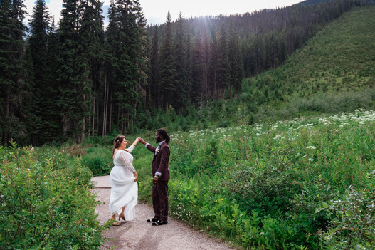Bride and groom dancing on a pathway with tall grass and wild flowers beside them.