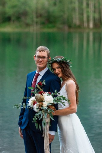 Bride and groom posing in front of the water in Kananaskis.