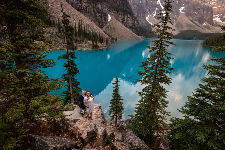 Bride and groom shot from far away. Couple is standing on rocks wth Moraine Lake in the background and mountains.