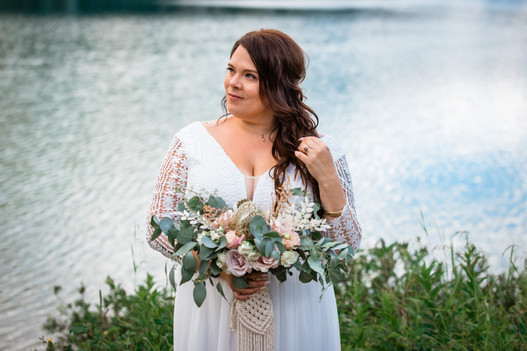 Bride standing alone in front of Emerald Lake touching her hair and holding her bouquet.