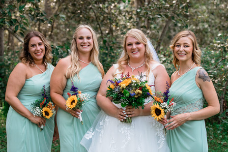 Bride standing with her bridal party, all holding sunflower bouquets.