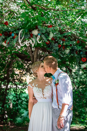 bride and groom sharing a kiss under a big tree.