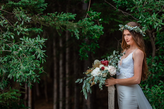 Bride standing alone in front of the trees holding her bouquet.