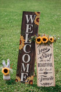 Wooden signs with sunflower accents at the ceremony.