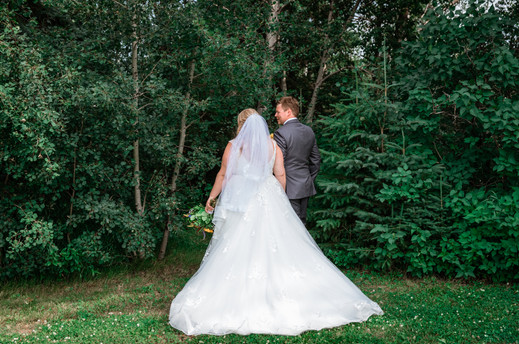 Bride and groom show from behind in front of the trees showcasing the brides dress.