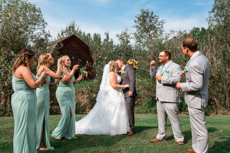 Bride and groom with their wedding party. Bride and groom are kissing.