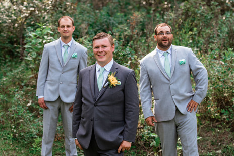 Groom with her groomsmen posing in front of the trees.