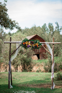 Wooden archway adorned with tule, flowers and greenery. Little red barn in the background.