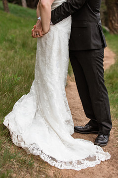 Bride holding the grooms hands behind her back. Photo shows the lower half of the couple