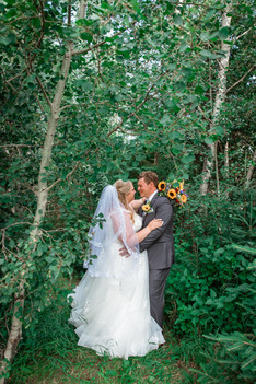 Bride and groom embracing, about to kiss. Bride is holding her bouquet and they are in front of trees.