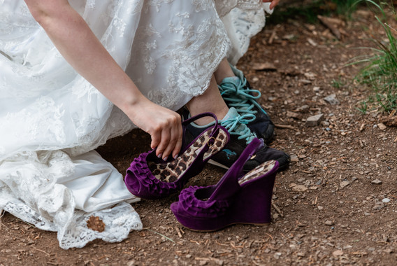 Bride in her dress changing shoes. Her wedding shoes are purple.
