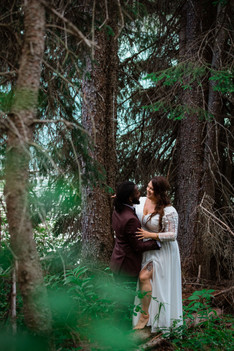 Bride and groom holding one another in the trees.