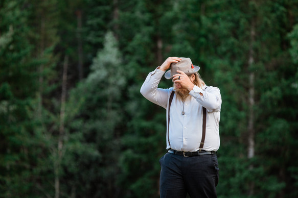 Groom standing fixing his fedora and is standing with all the trees behind him.