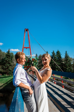bride and groom standing on a suspension bridge. The bride is pulling on the grooms suspenders.