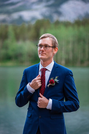 Groom standing alone in front of the water in Kananaskis.