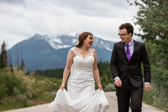 Bride and groom walking down the street looking at one another laughing