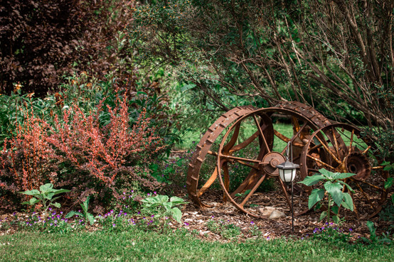 Antique wheels against a tree and a lantern.