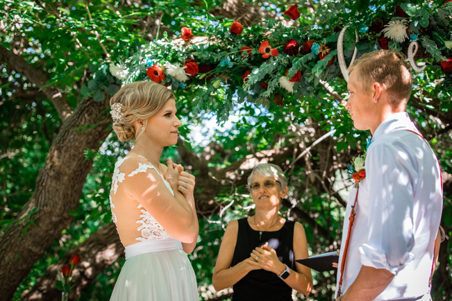 bride signing her vows to her groom under a big tree.