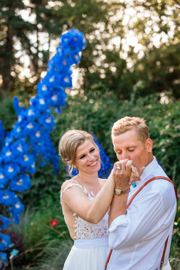 bride and groom dancing and the groom is kissing the brides hands as she looks at him lovingly.