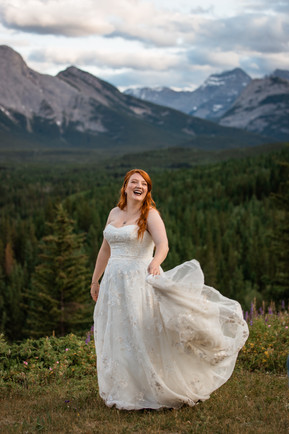 Bride laughing holding up the bottom of her dress. Lots of trees in the background.
