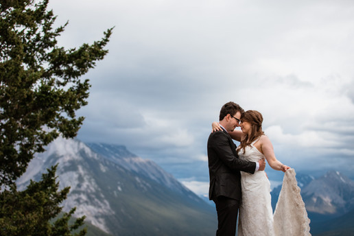Bride and groom in front of a stunning scenery embracing. Bride is holding up the end of her dress.