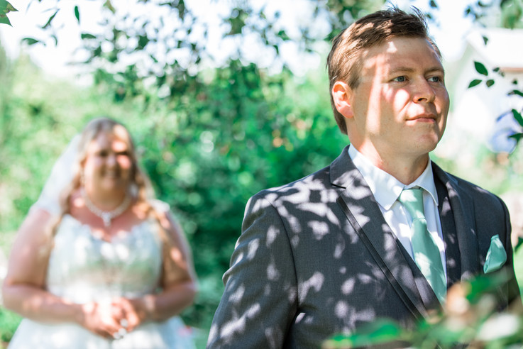 The grooms face waiting to see his bride for the first time, She is standing behind him.