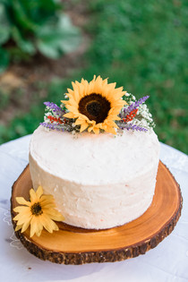 Wedding cake with sunflowers on it.