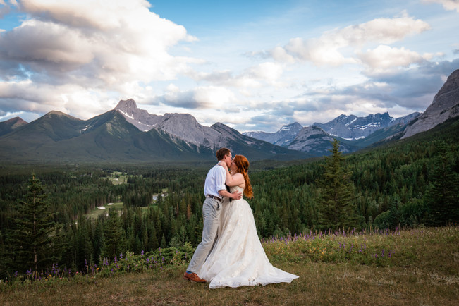 Bride and groom kissing with mountains and trees in the background.