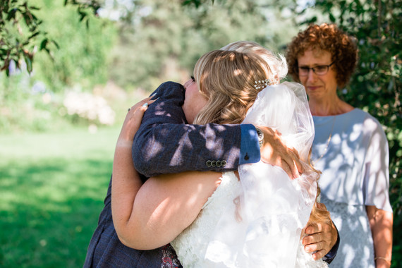 Emotional moment of the bride hugging her father with her tearful mother beside them.