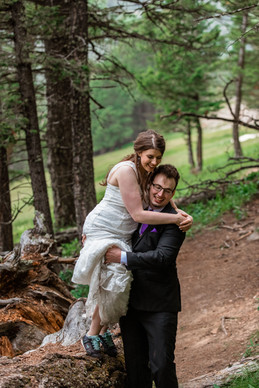 Groom is carrying the bride in the forest in Banff National Park