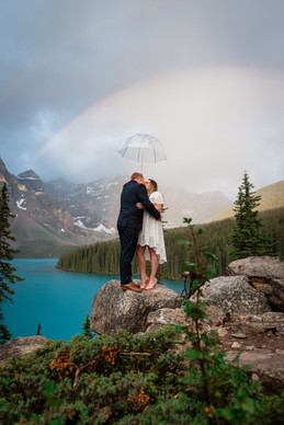 Bride and groom kissing under an umbrella on a big rock overlooking Moraine Lake.