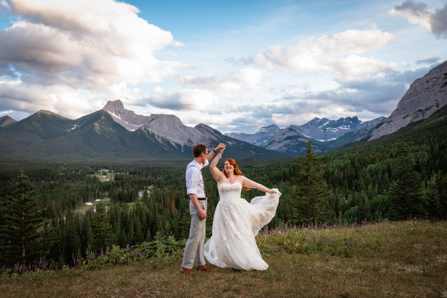 Groom twirling his bride and she is holding up the train of her dress. Mountains in the background.