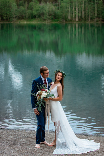 Bride and groom standing in front of water in Kananaskis.