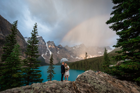 Bride and groom standing under an umbrella with Moraine Lake in the background and a rainbow in the sky.