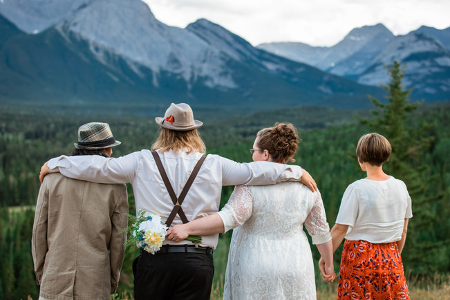 Wedding party from behind with their arms around one another looking to the mountains.