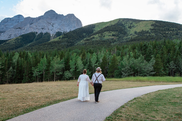 Bride and groom walking on a path holding hands. Trees and mountains in the background.